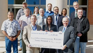 Scott James, Lockheed Martin manager of production engineering, front row from left, Charley Jackson, Lockheed Martin HR business partner, give a $20,000 check to SAU President Dr. Trey Berry for SAU Engineering with representatives from SAU's growing program looking at in front of the Science Center.
